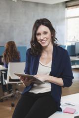 lächelnden Frau mit Tablet-PC sitzt an ihrem Arbeitsplatz in der Großraumbüro