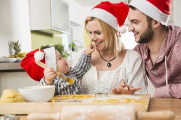 Familie trägt Weihnachtsmützen beim Backen in der Küche