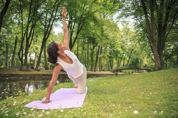 Frau trainiert Yoga in einem Park