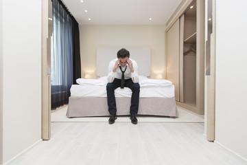 Geschäftsmann mit Kopf in seinen Händen, auf Hotelbett sitzend