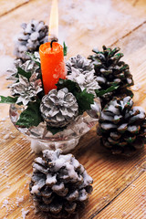 Christmas candle is decorated with pine cones
