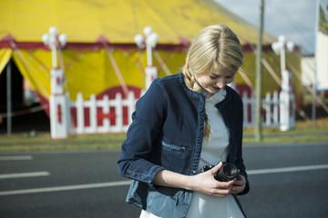Deutschland, Mannheim, junge Frau mit Kamera vor Zirkuszelt