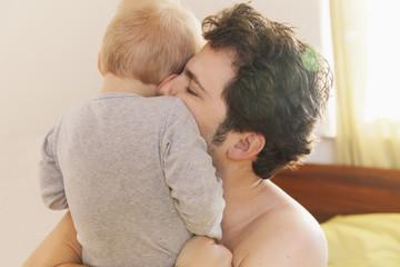 Vater beim Kuscheln mit seinem kleinen Sohn