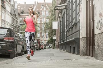Deutschland, Niedersachsen, Hannover, junge Joggerin auf dem Bürgersteig laufend