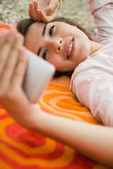 Lächelnde junge Frau liegend auf Handtuch