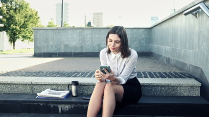 Businesswoman listening to music on smartphone on stairs in the