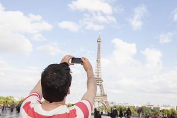 Frankreich, Paris, Eiffelturm, Mann fotografiert mit seinem Smartphone, Blick zurück