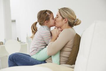 Deutschland, München, Mutter und Tochter sitzen auf dem Sofa