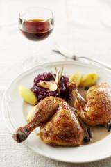 Gebratene Hähnchenkeule mit Morchelsauce, Rotkohl und Kartoffeln auf Teller
