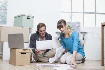 Zwei Kollegen sitzen auf dem Boden zwischen Kartons in einem Büro