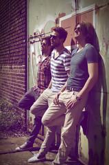Drei junge Männer warten vor altem Industriegebäude