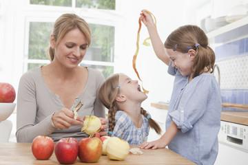 Mutter schält Apfel, Mädchen spielen mit Schalen