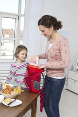 Mutter und Tochter packen Rucksack am Morgen