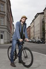 Deutschland, Bayern, München, junger Mann auf Bürgersteig mit seinem Rennrad