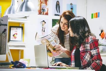 Zwei weibliche Modeblogger mit Magazinen im Büro