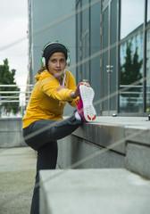 Junge Frau mit gelber Trainingsjacke macht Stretching-Übungen
