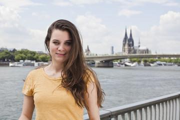 Deutschland, Köln, Lächelnde junge Frau am Rhein