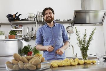 Lächelnder Man,n Vorbereitung Kartoffeln in der Küche