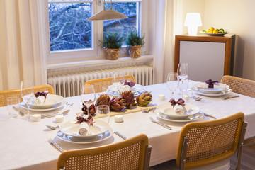 Gedecke und Dekoration mit Artischocken auf festlich gedecktem Tisch am Abend