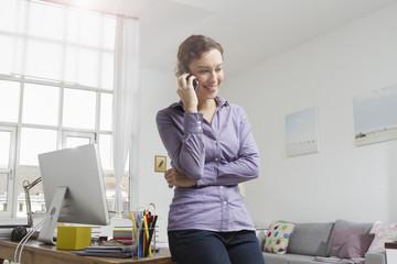 Frau lehnt am Schreibtisch mit Handy