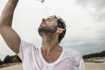 Mann gießt Wasser aus der Flasche über sich selbst