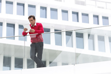 Geschäftsmann mit Tablet-Computer, vor Hotel