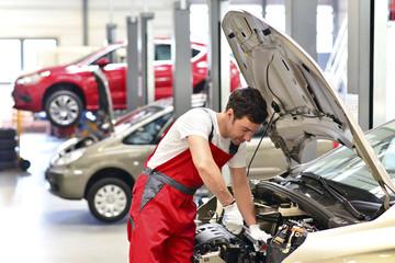 Kfz-Mechaniker in einer Werkstatt arbeitet an Auto