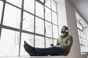 Junger Mann sitzt auf der Fensterbank in einem Büro, hört Musik mit Kopfhörer