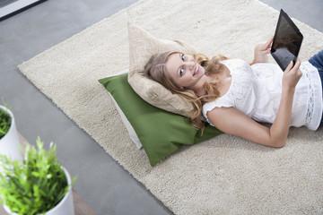 Junge Frau mit Tablet-Computer auf einem Teppich liegend