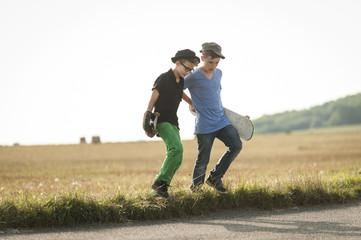 Zwei Jungen zu Fuß über ein Feld mit ihren Skateboards