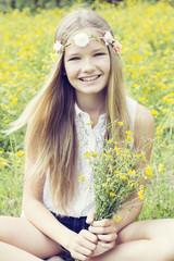 Portrait eines glücklichen Mädchens, sitzend auf einer Blumenwiese