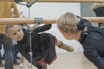 Junge Eiskunstläuferin beim Stretchen