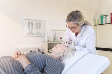 Heilpraktikerin gibt älterer Frau Injektionsakupunktur