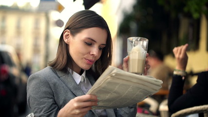 Businesswoman reading newspaper and drinking coffe, sitting in c