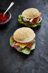 Zwei vorbereitete Burger, Senf und Ketchup auf dunklem Grund