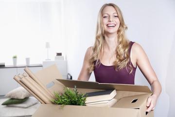 Lächelnde junge Frau mit Karton