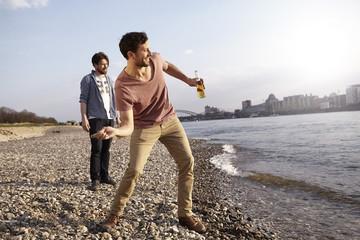 Zwei Freunde werfen Steinchen in Fluss