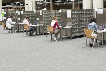 Studenten in einer Universitätsbibliothek mit Laptops