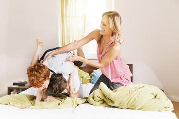 Junge Familie ausgelassen auf dem Bett