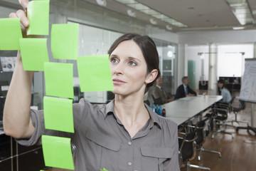 Geschäftsfrau im Büro, Haftnotizen auf Glasscheibe