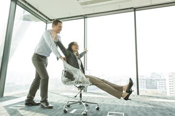 Unternehmer schiebt Geschäftsfrau im Bürostuhl
