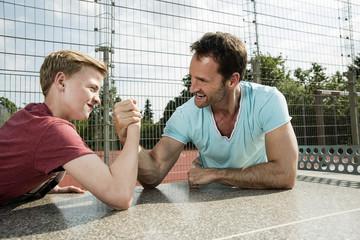 Vater und Sohn beim Armdrücken