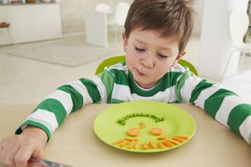 Deutschland, München, Junge isst Erbsen und Möhren, skeptisch