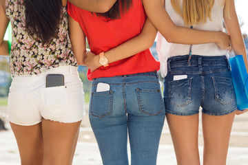 Three students girls with mobile in the pocket.