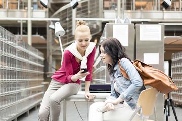 Zwei Studenten mit Handy in einer Universitätsbibliothek