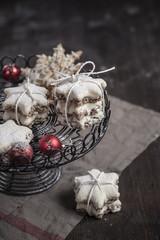 Mit Puderzucker bestreut, sternförmige Zimt-Kekse und rote Christbaumkugeln
