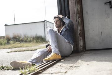 Cooler Mann sitzt auf dem Boden