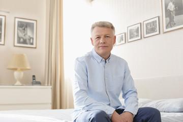 Portrait von reifem Mann, sitzt auf dem Bett