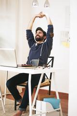 Mann bei Dehnübung im modernen Büro zu Hause