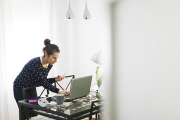 Junge Frau arbeitet mit Laptop zu Hause